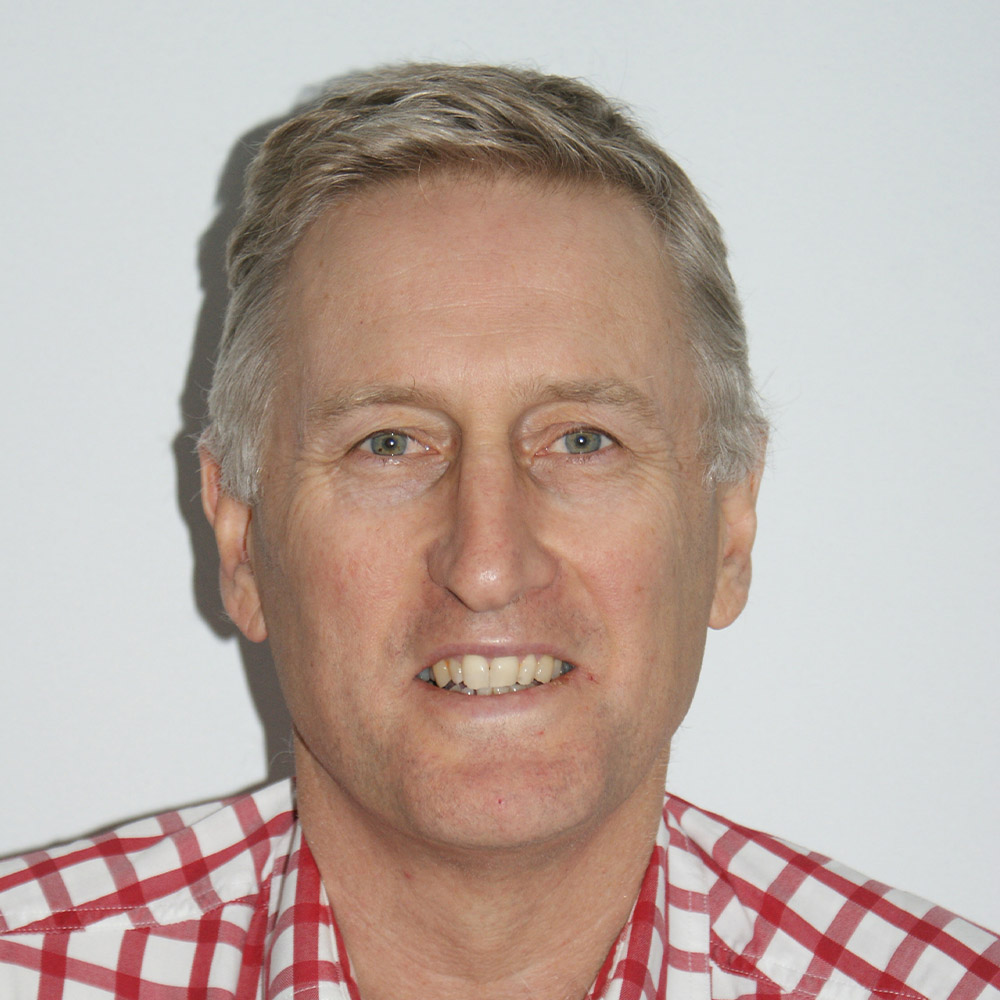 A portrait photo of Mecardo external team member Andrew Woods, in front of a white background wearing a blue and white checked shirt