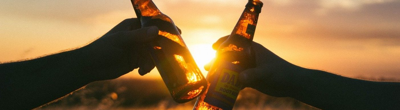 Image of two arms holding beer bottle with sunset and crop in background